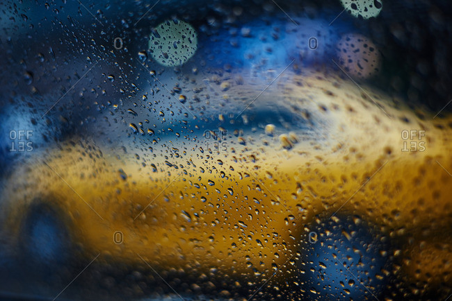 Blurred shape of yellow taxi cab seen from raindrop-covered window of passing car in blue twilight colors of New York evening