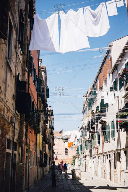 Venice, Italy - August 31, 2016: People walking on street in Venice with laundry drying on clothes lines