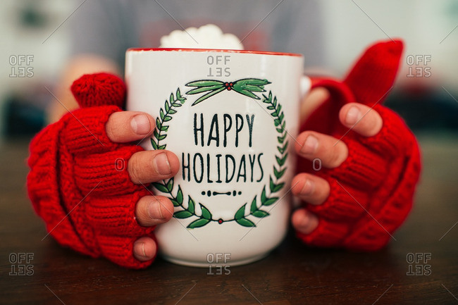 Child wearing fingerless gloves holding a mug of hot chocolate