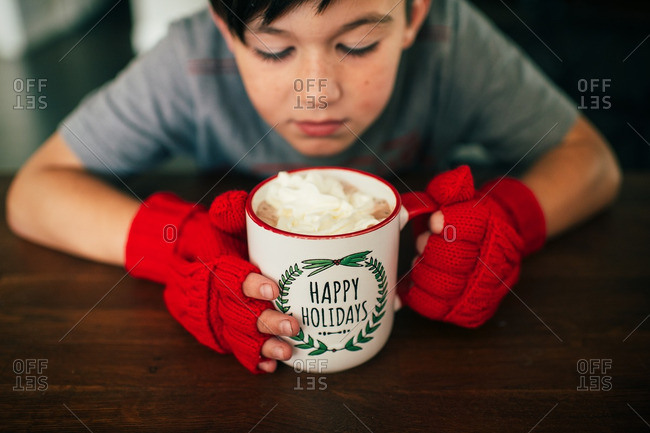 Boy wearing fingerless gloves holding a mug of hot chocolate
