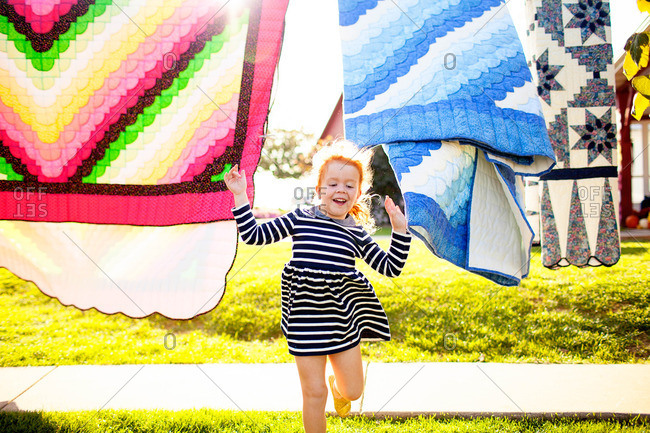 Little girl running through blankets drying on a line outdoors