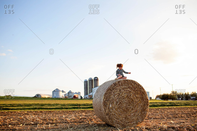 Little girl sitting on a large bale of hay in the countryside