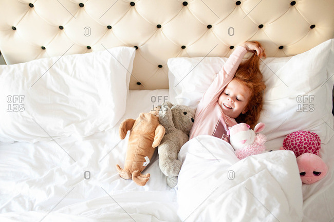 Little girl lying in bed with her stuffed animals