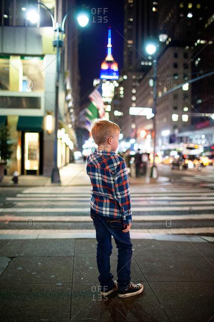 Boy standing on city sidewalk corner