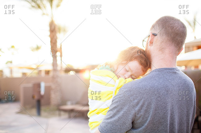 Father carrying sleeping daughter outside