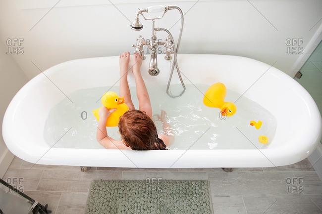 Little girl taking a bath with rubber ducks