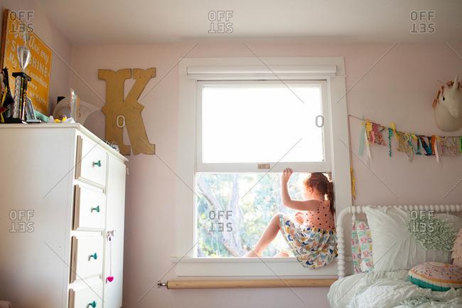 Little girl sitting in her bedroom window looking outside