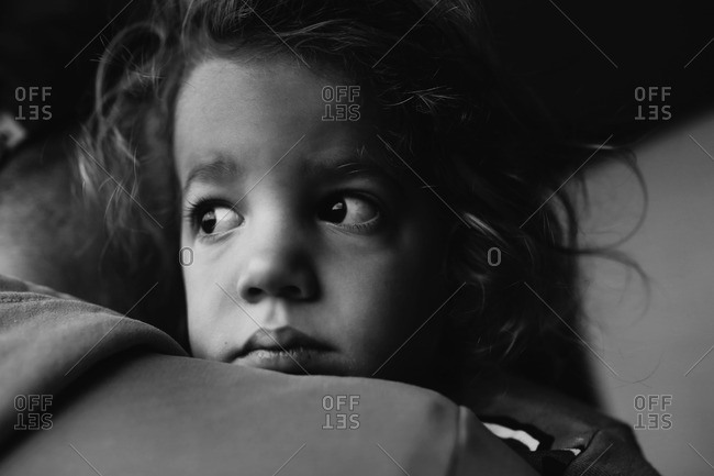 Toddler looking over father's shoulder with worried expression