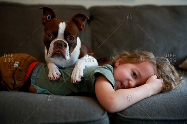 Little boy relaxing on couch with his dog