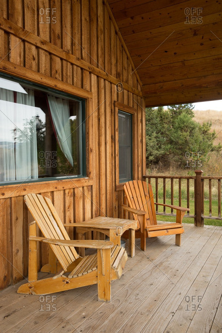 A cabin porch with Adirondack chairs