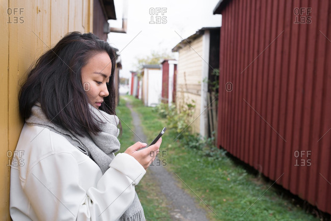 Woman leaning on side of building using Smartphone