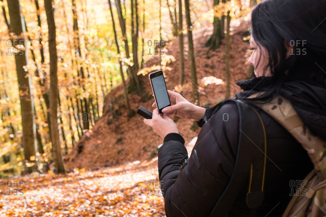 Woman taking picture of a forest in autumn with a Smartphone