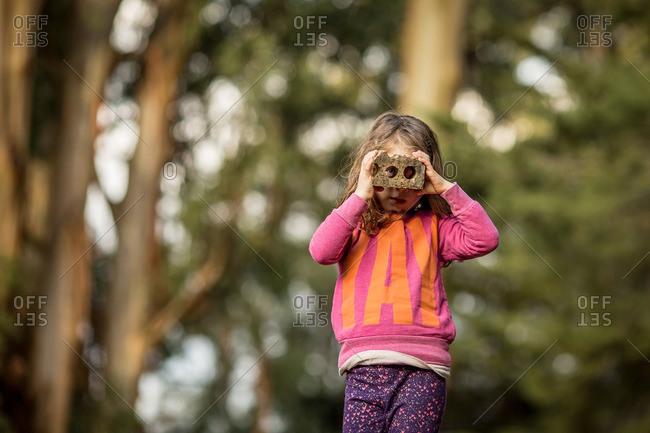 Girl looking through brick as binoculars