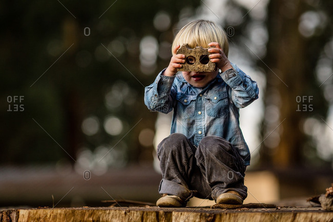 Boy looking through brick as binoculars