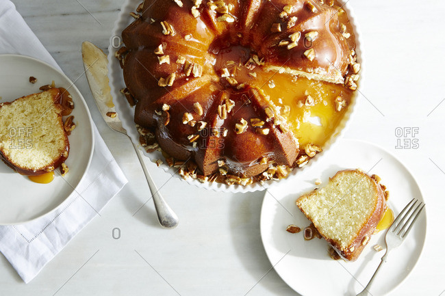 Bundt cake topped with nuts and dripping with caramel