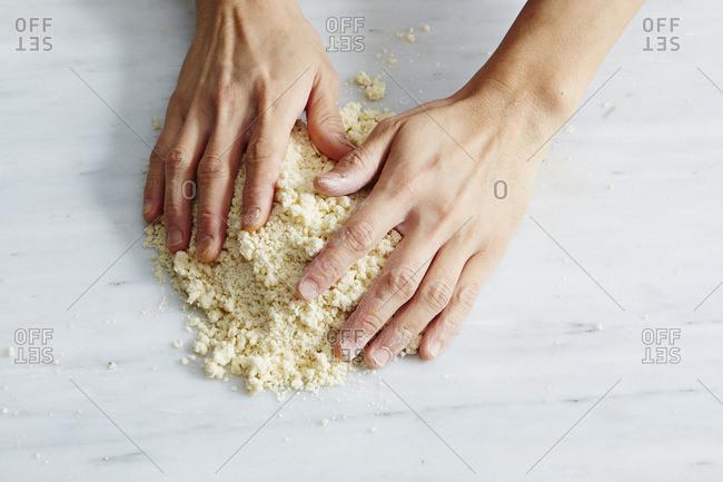 Hands forming dough