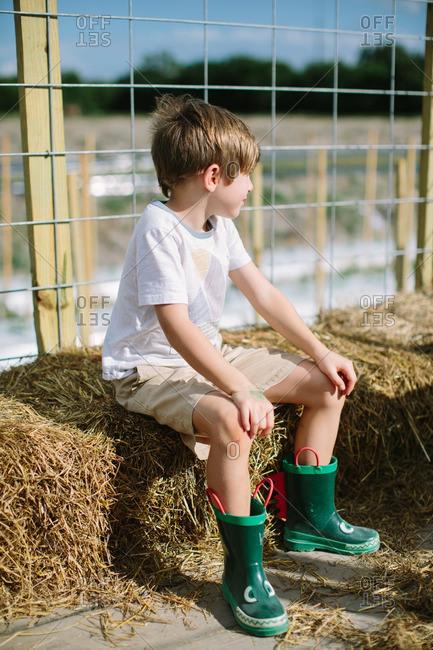 Boy sitting on a hay bale on a hay ride