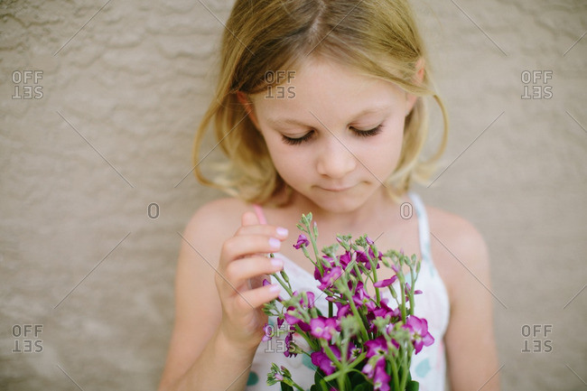 Blonde girl holding bunch of purple flowers