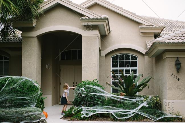 Girl placing spider webs on bushes