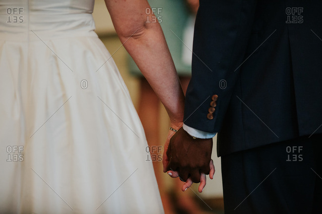 Interracial bride and groom holding hands