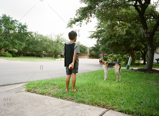 Young boy playing ball with his dog