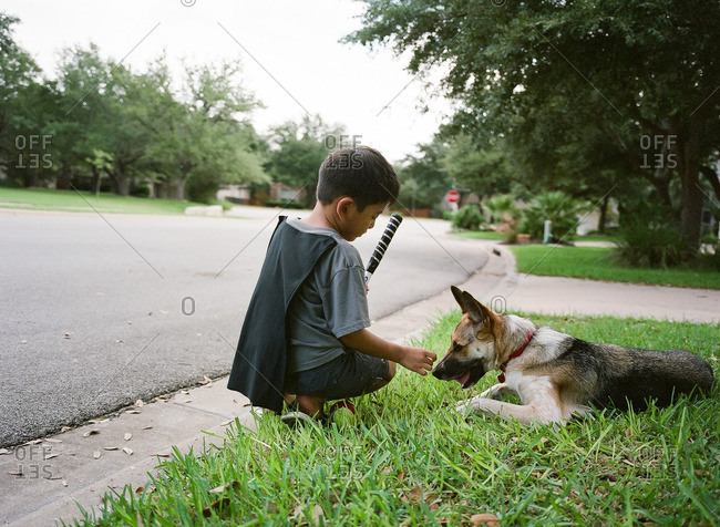 Young boy sitting in the grass with his dog