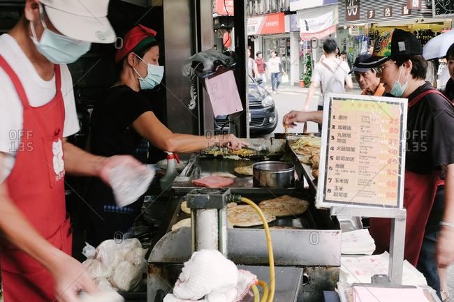 Taipei, Taiwan - June 22, 2013: Street vendors making green onion pies, Taipei, Taiwan