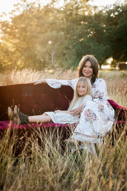 Mother and daughter sitting close together on a couch in a grassy meadow and natural setting
