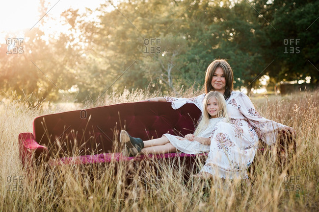 Mother and daughter sitting close together on a sofa in a grassy field and natural setting