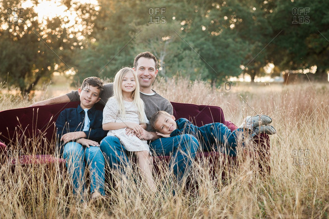 Father and his children sitting together on a sofa in a grassy field and natural setting