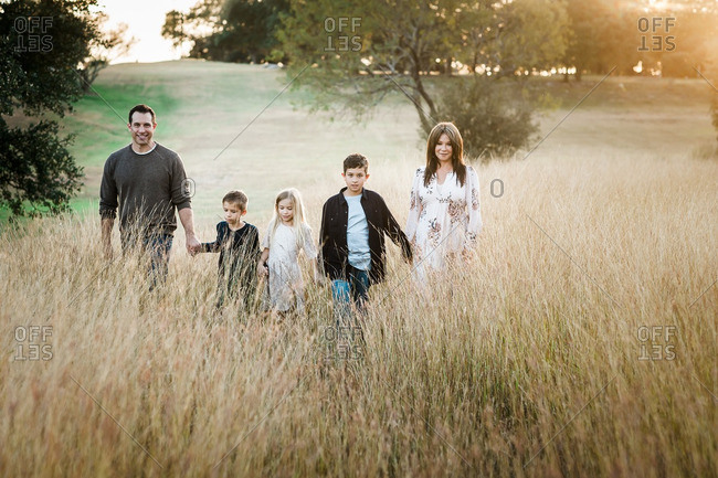 Family holding hands and walking together in a field of tall grass