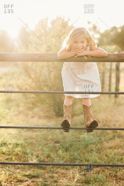 Portrait of a smiling girl wearing cowboy boots looking over the railing of a fence