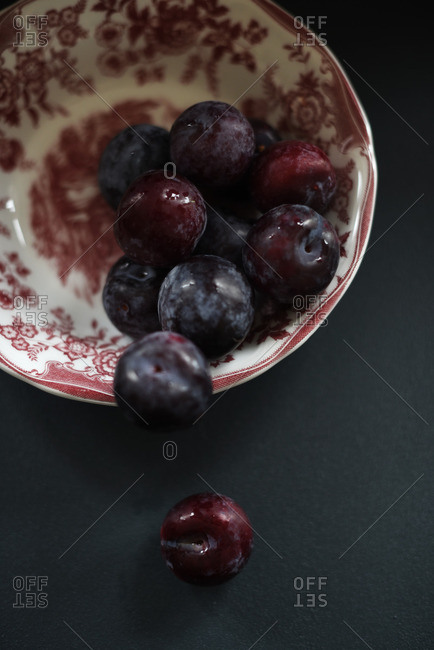Purple plums in a vintage red bowl