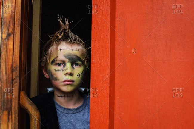 Young boy dressed up as a monster looking out a red door