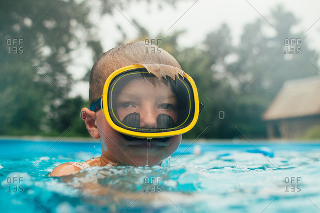 Young boy, 6-7 years old swimming in swimming pool