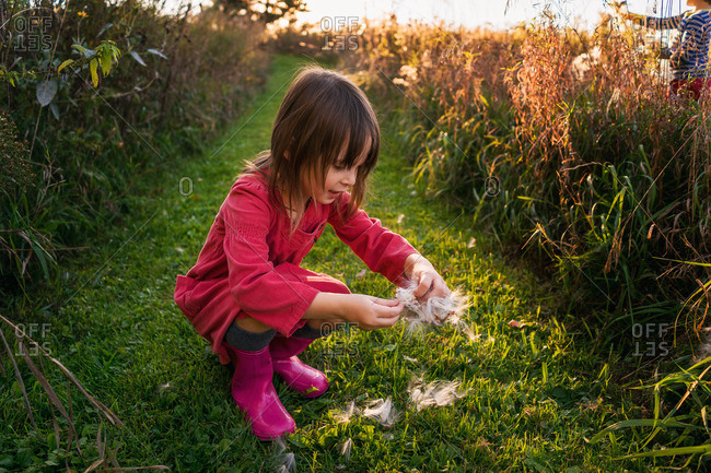 Young girl playing with milkweed in a field