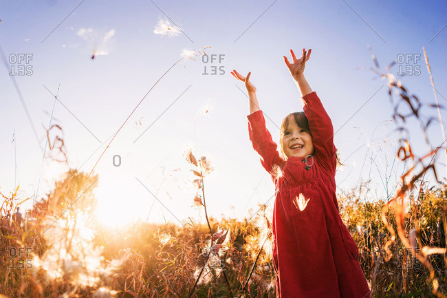 Young girl throwing milkweed in a field
