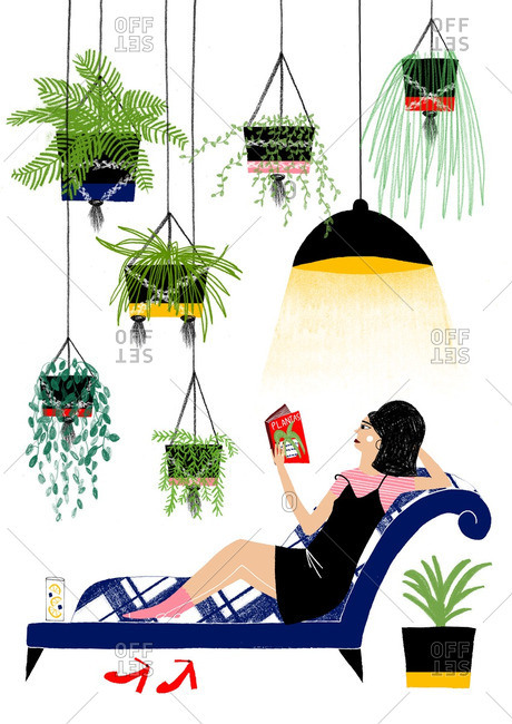 Woman reading book on chaise surrounded by plants