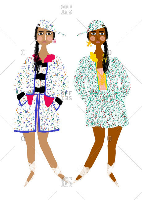 Two women in brightly patterned clothing with matching caps