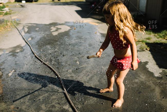 Girl playing with spraying hose