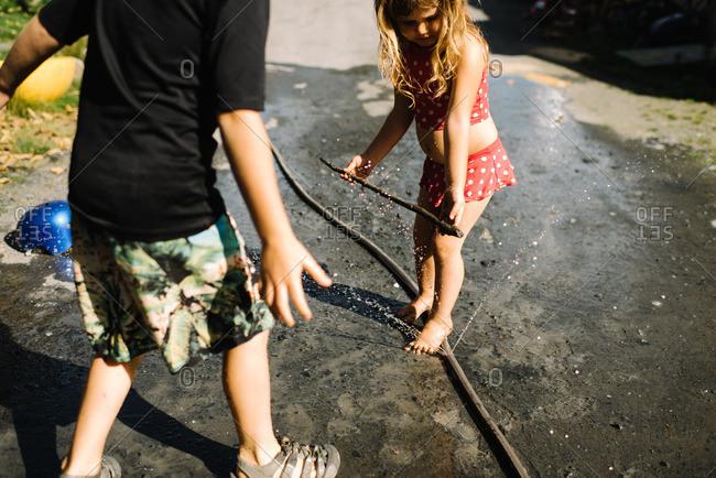Kids playing by hose spraying water