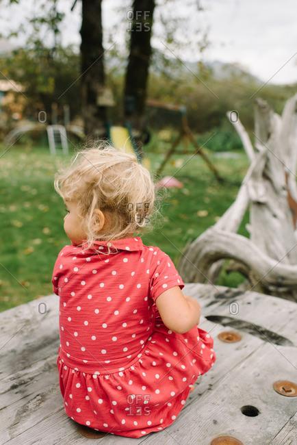 Girl in polka dot dress on outdoor table