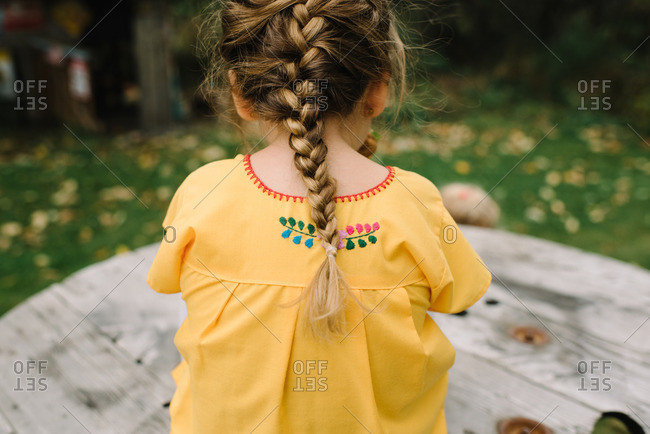 Girl in pigtail and embroidered shirt