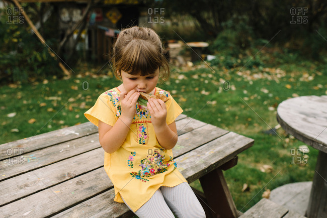 Girl sitting on picnic table eating sandwich
