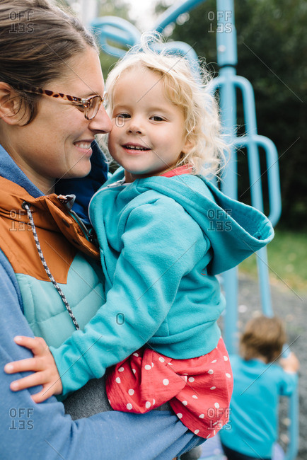 Mom holding girl in playground