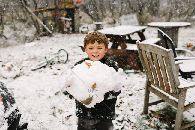 Boy in yard holding large snowball