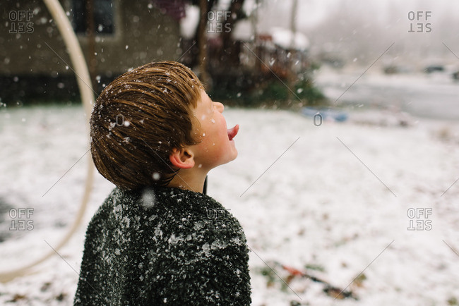 Boy catching snowflakes with tongue