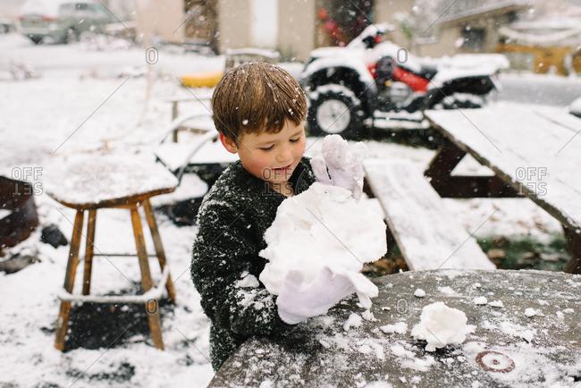 Boy making a snowball in yard