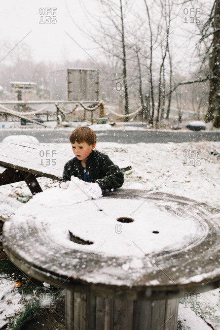 Boy collecting snow off yard table