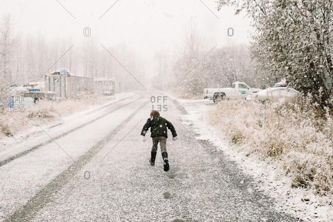 Boy running on road in snowstorm